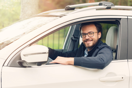 happy young man sitting in the car